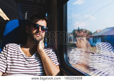 Young man traveling on a train sitting by the window