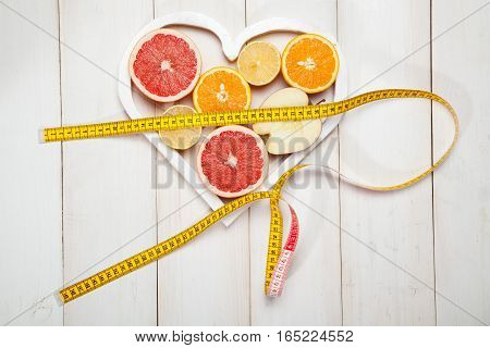Fruits in heart and centimeter on a white background
