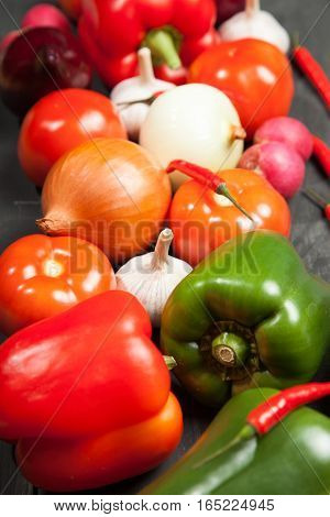 Vegetables. Peppers, tomatoes, garlic, eggplant, onions and radishes on a black background