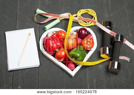 Sport and diet. Healthy lifestyle. Vegetables, dumbbells and notebook. Peppers, tomatoes, garlic, onion and radish in a heart on a black background