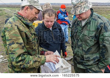 Mullashi, Russia - April 29, 2007: Tourists on bicycle met hunters near Duvan river and specify route on map