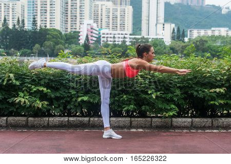 Professional female athlete practicing yoga horizontal balancing stick pose standing on one leg keeping balance in summer city park.