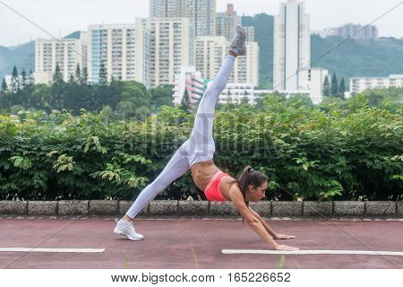 Young slim woman doing yoga down dog split exercise in city park on summer day. Female athlete stretching in standing position with arm support