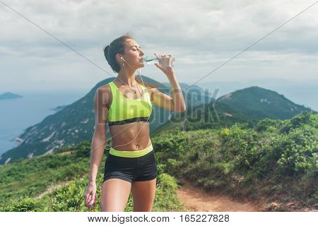 Fitness woman drinking water from a bottle relaxing after working-out listening to music standing on grassy mountain in summer