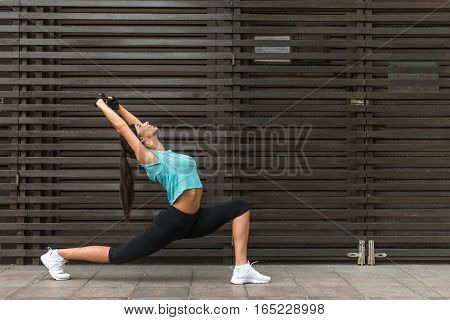 Fit young woman stretching by doing yoga low lunge exercise outdoors on the city street