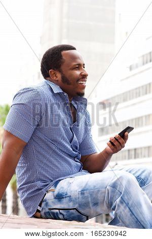 Side Portrait Of Smiling Man Sitting In City With Cellphone