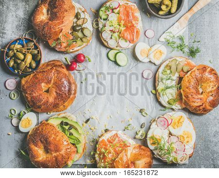 Variety of bagels with salmon, eggs, radish, avocado, cucumber, greens and cream cheese for breakfast, healthy lunch or party over grey concrete background, top view, copy space. Takeaway food concept