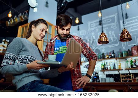 Young people at a cafe looking notebook. Couple with the laptop  in bar.