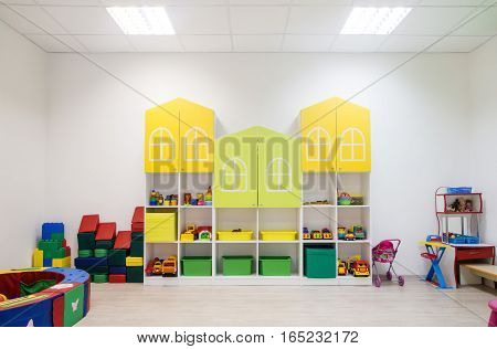 Light interior of a modern kindergarten in yellow and green colors.