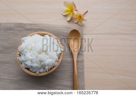 Cooked rice in a wooden bowl and spoon on a wood background.