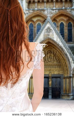 back of red head bride in front of church waiting