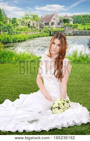 portrait red head bride with bouquet sitting by lake