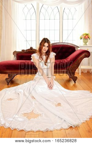 portrait of red head bride sitting on floor by window