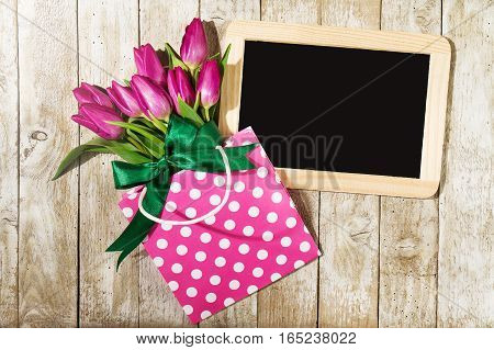 Fresh beautiful lila tulips in gift package on wooden background with chalkboard. Spring concept. Horizontal top view with copy space.