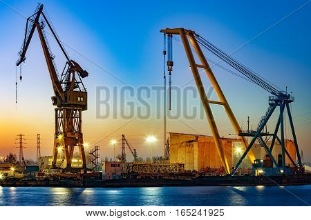 Floating crane at night in port .