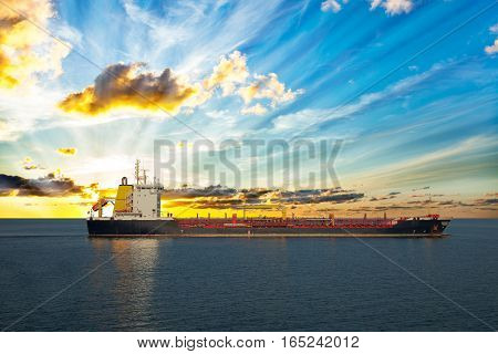Sun setting at the sea with tanker ship.