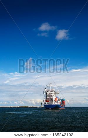 Cargo ship just leaving Gdynia harbour. Vertical frame. Poland.