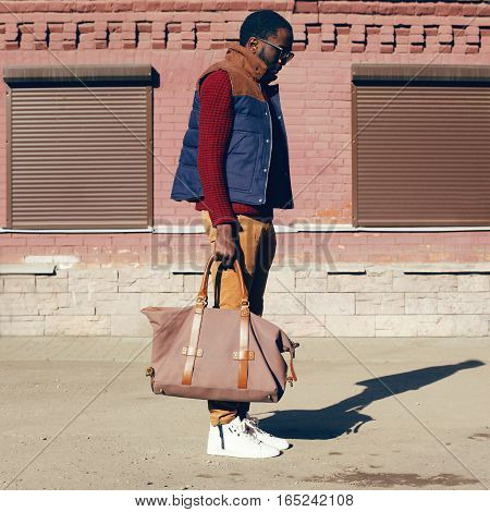 Street Fashion Look Concept Stylish African Young Man Wearing Vest Jacket, Sweater, Bag Walking In C