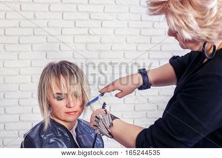 Women's haircut. hairdresser, beauty salon. Professional hairdresser making stylish haircut. Hairdresser cutting woman bangs hair. Process of hair cutting with use open-blade