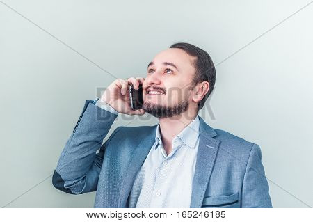 Man talking on the phone looks up and smiles. Businessman happy about the good news.