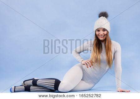 Fit woman in full length wearing winter cap gray sports thermal underwear warm socks studio shot on blue. Long sleeves top and leggings.