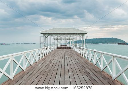 Wooden walk way leading to white pavilion on the seacoast skyline Thailand