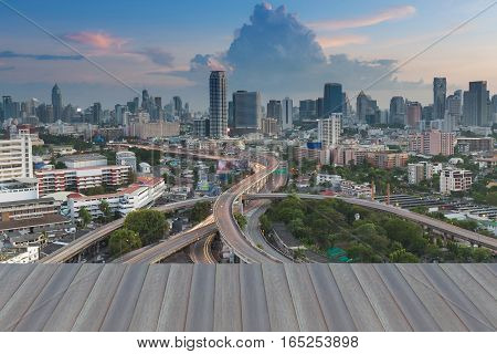 Opening wooden floor Bangkok city background over highway intersection Thailand