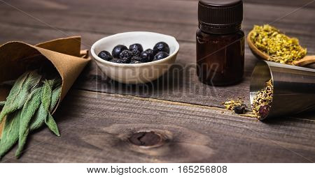 Many different medicinal herbs  on a dark wood background. Homeopathic pills.
