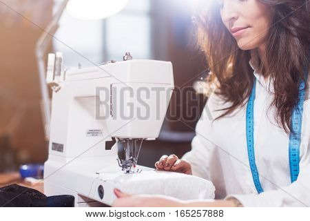 Close-up view of sewing machine and young female tailor working on it while sitting in a workshop.