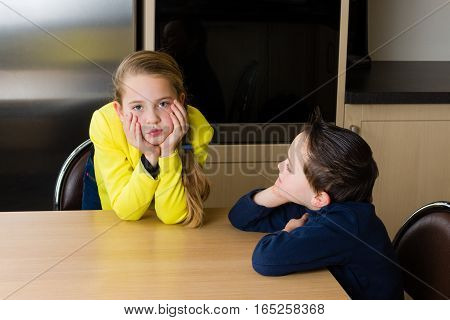 Kids (siblings boy and girl) are arguing at the kitchen table