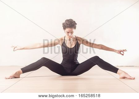 Slim young ballet dancer doing stretching exercise sitting with her legs wide apart indoors.