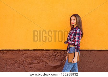 beautiful stylish smiling women with tablet . Orange background. Copy-space. Outdoor
