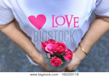 Woman holding a beautiful red roses . Valentine's day concept.