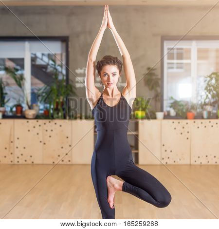 Fit woman practicing yoga exercise called Tree Pose standing on one leg indoors.