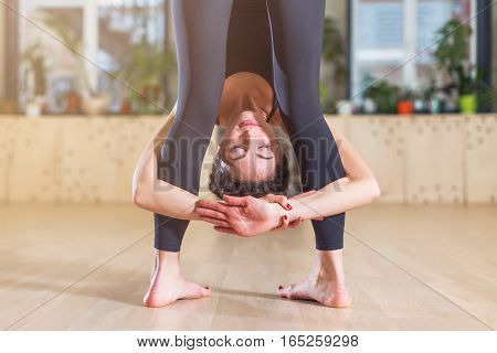 Close-up view of female yogi with her head between the legs while standing in forward bending yoga pose indoors