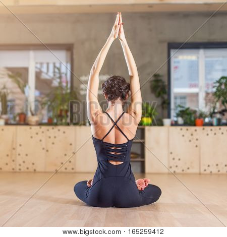 Rear view of slim woman doing yoga exercise meditating sitting in lotus pose with arms raised up.