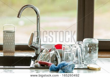 Washing up. Modern sink and kitchen counter with claen dishwares window in the background