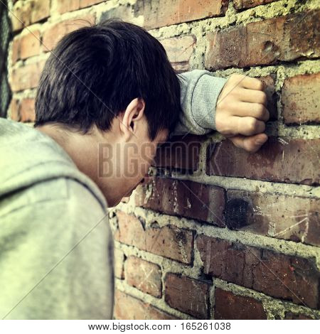 Toned Photo of Sad Young Man by the Wall outdoor