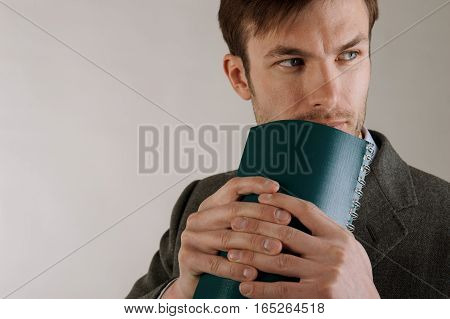 businessman with a notebook in hand thinks and looks