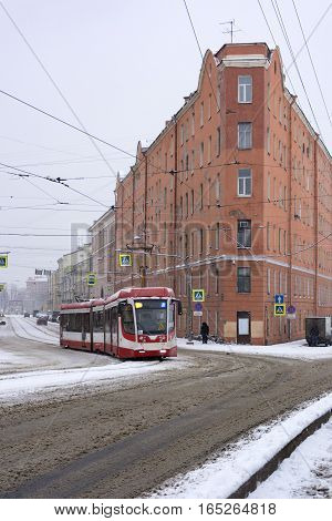 red white tram rides on the road the street the city old buildings rails wires snow winter Saint-Petersburg Sadovaya Russia
