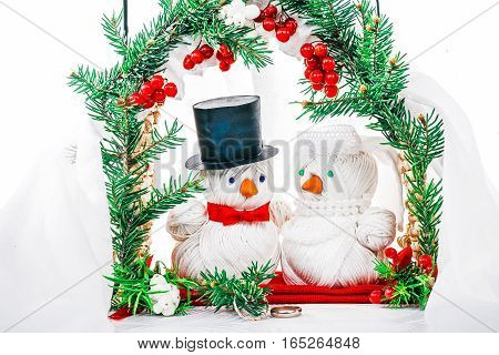 Wedding ceremony of toy yarn snowmen couple under winter decorated arch. Concept of winter weddings