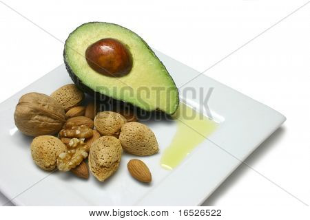 Avocado, walnuts and almonds, puddle of olive oil on white plate, isolated on white - foods rich in good oils
