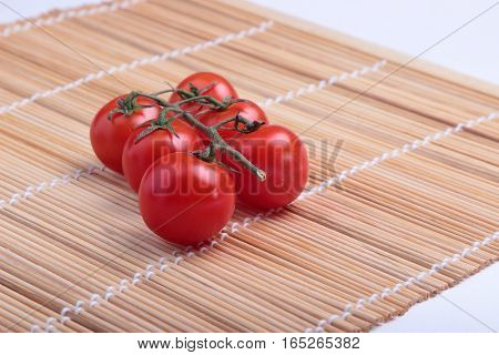 red cherry tomatoes on a bamboo Mat