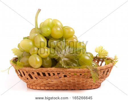 green grapes in a wicker basket isolated on white background.