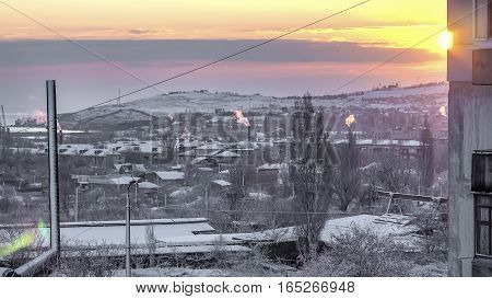 The rising sun in the snow city and over the factory