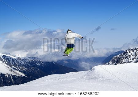 Snowboarder Jumping In Terrain Park At Ski Resort On Sun Winter Day