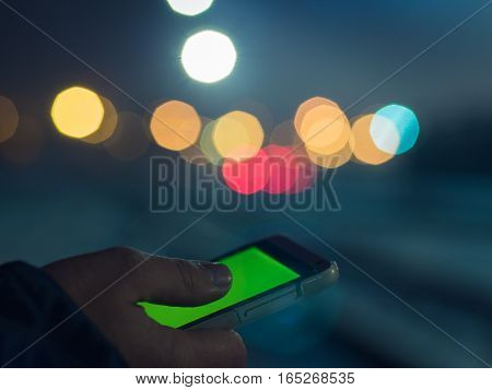 Closeup of male hands using modern smartphone at night, bokeh light in blurred background, social network concept, night lights