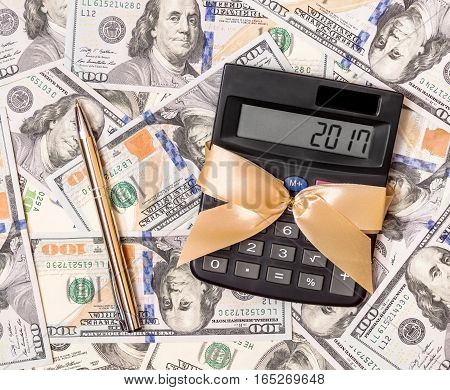 2017 year written on the display of calculator which is on dollars background. Business concept.