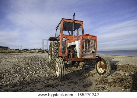 Vintage red diesel tractor engine on the beach