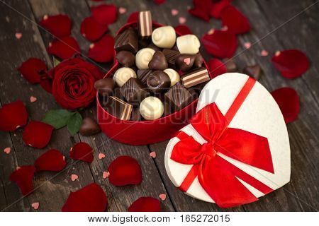 Red roses and chocolate pralines in red heart shaped gift box background